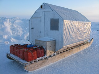 Traveling shelter built on Komatik sled with gas jugs tied on the back.