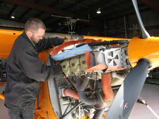 Expert mechanic, at Dakota Helicopters, Bo Klindworth doing an oil change and inspection on the Polar Pumpkin.